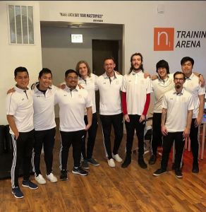 Ryan Kim (left) standing with his coaches at N1 Esports.